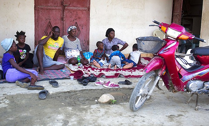 Genson Jean Baptiste and his family gather outside their home on Monday after a 5.9 earthquake that hit Haiti over the weekend, in Port-de-Paix. (AP)