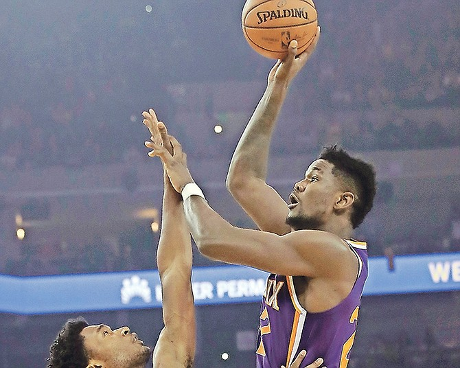 Phoenix Suns centre Deandre Ayton, right, shoots against Golden State Warriors centre Damian Jones in the first half on Monday night in Oakland, California. The Warriors won 123-103.