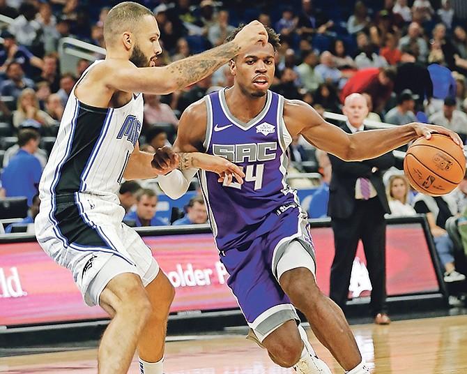 Sacramento Kings' Buddy Hield (24) drives around Orlando Magic's Evan Fournier, left, in the first half on Tuesday night.  (AP Photo/John Raoux)