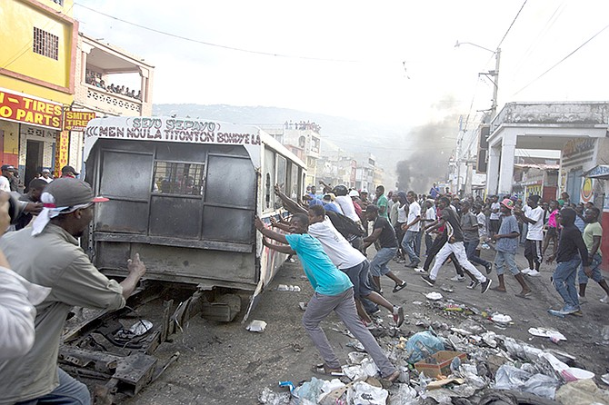 DEMONSTRATORS push a broken bus to burn at a barricade during an opposition protest in Port-au-Prince, Haiti, Sunday.