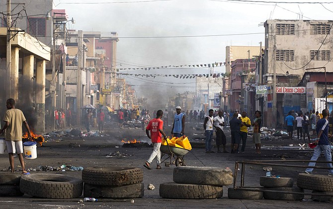 Residents walk amid road blocks placed by anti-government protesters along Boulevard Jean-Jacques Dessalines, a main commercial artery, during a strike against alleged government corruption in Port-au-Prince, Haiti, Wednesday. (AP)