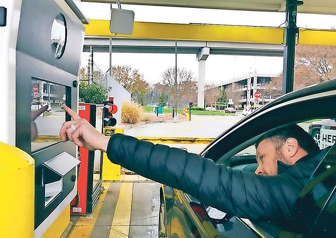 A rental car driver demonstrates a new biometric scanning machine by placing his finger on the reader at the Hertz facility at Hartsfield-Jackson Atlanta International Airport, in Atlanta. In a first for the rental car industry, Hertz is teaming up with Clear, the maker of biometric screening kiosks found at many airports and stadiums. Hertz says the partnership will slash the time it takes to pick up a rental car. Photo: Jeff Martin/AP