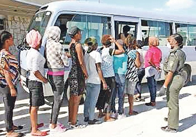 Haitian migrants boarding a bus to be transported to the Carmichael Road Detention Centre. Photo: Chief Petty Officer Jonathan Rolle/RBDF