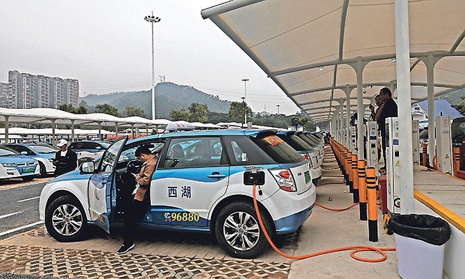 New electric-powered taxis are charged at a public charging station in Shenzhen city, south China's Guangdong province. Photo: Vincent Yu/AP