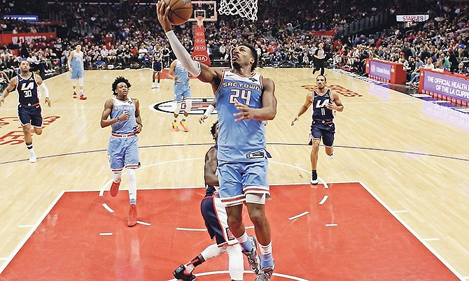 Sacramento Kings' Buddy Hield (24) scores against the Los Angeles Clippers during the first half Sunday in Los Angeles.