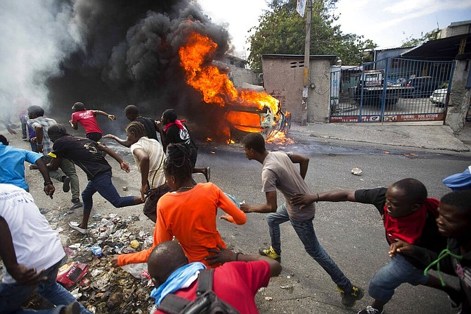 Demonstrators run away from police who are shooting in their direction, as a car burns during a protest demanding the resignation of Haitian President Jovenel Moise in Port-au-Prince, Haiti, last week. (AP)