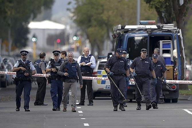 Police officers search the area near the Masjid Al Noor mosque, site of one of the mass shootings at two mosques in Christchurch, New Zealand, Saturday. (AP)