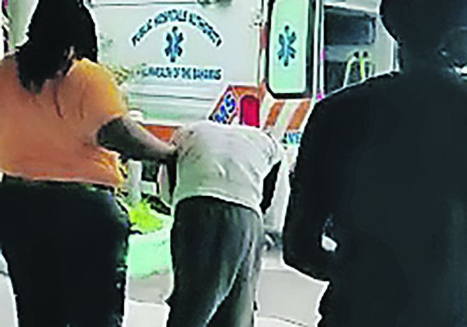 The suspect is helped to a waiting ambulance in a still from the video.