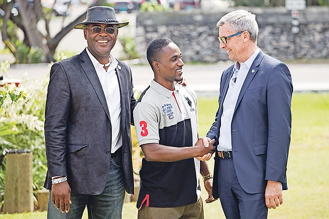 Shervano Johnson, 25, centre, gets words of encouragement from Royal Caribbean International president and CEO Michael Bayley, right. Also pictured is Pinewood MP Reuben Rahming.