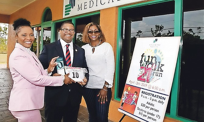 Deputy Prime Minister K Peter Turnquest receives his race kit from Shandra Moss-Styles (left), retention manager with Atlantic Medical Freeport, and Lisa Turnquest, office manager in Freeport.