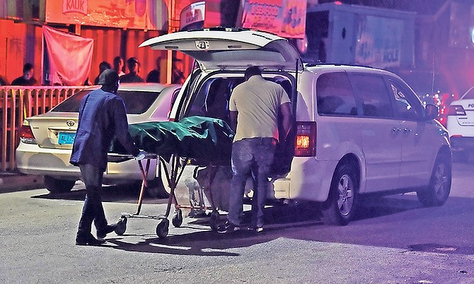 One of the bodies is removed from the scene on Wednesday night. Photo: Shawn Hanna/Tribune Staff