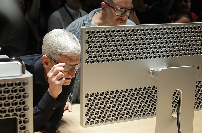 Apple CEO Tim Cook, left, and chief design officer Jonathan Ive look at a Mac Pro in the display room at the Apple Worldwide Developers Conference in San Jose, Calif., Monday. (AP Photo/Jeff Chiu)