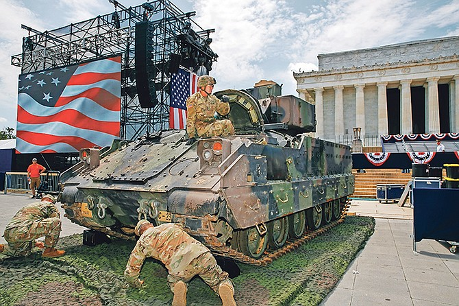 An Army soldier hops out of a Bradley Fighting Vehicle after moving it into place by the Lincoln Memorial yesterday in Washington, ahead of planned Fourth of July festivities with President Donald Trump.