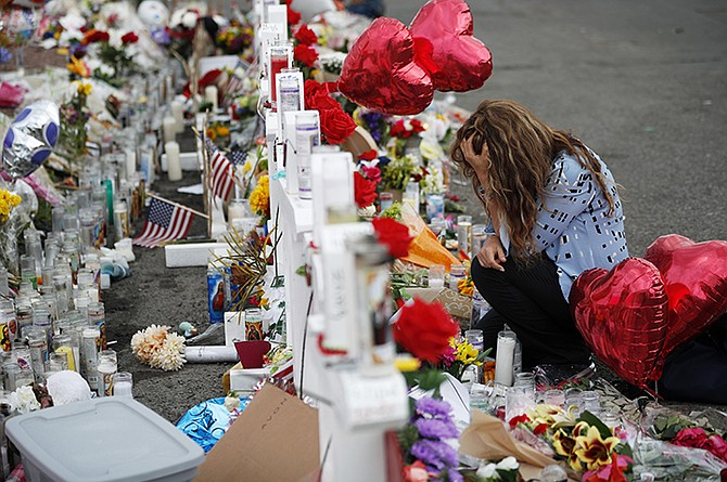 A woman kneels in front of crosses at a makeshift memorial near the scene of the mass shooting at a shopping complex in El Paso, Texas. (AP)