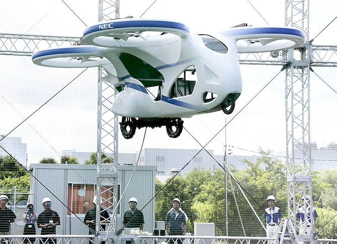 NEC Corp.'s machine with propellers hovers at the company's facility in Abiko near Tokyo, Monday. The Japanese electronics maker showed a 'flying car' – a large drone-like machine with four propellers that hovered steadily for about a minute. (AP Photo/Koji Sasahara)