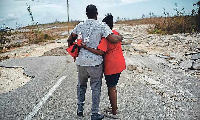 A couple embraces on a road destroyed by Hurricane Dorian as they walk to the town of High Rock to try and find their relatives in the aftermath of Hurricane Dorian in Grand Bahama yesterday. Photo: Ramon Espinosa/AP