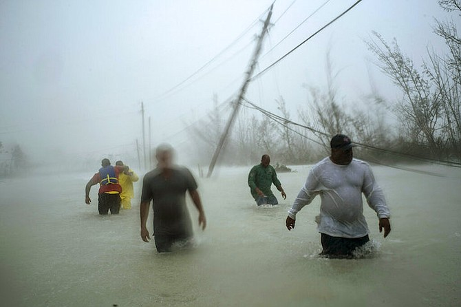 Volunteers wade through a flooded road against wind and rain caused by Hurricane Dorian to rescue families near the Causarina bridge in Freeport on Tuesday. (AP)