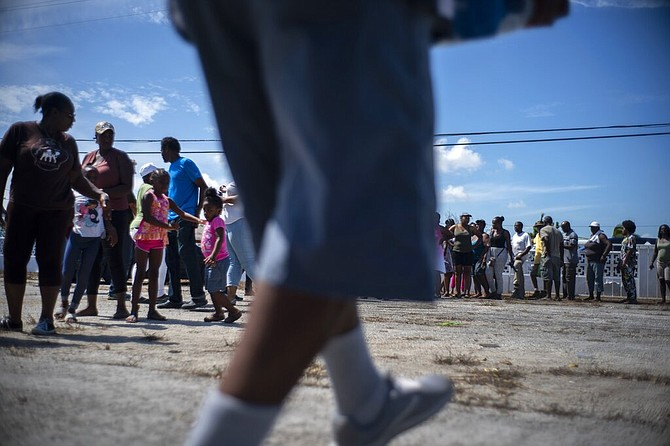 People form a line to receive paper towels and bottled water donated by private entities to victims of Hurricane Dorian, in Freeport,, Saturday. (AP Photo/Ramon Espinosa)