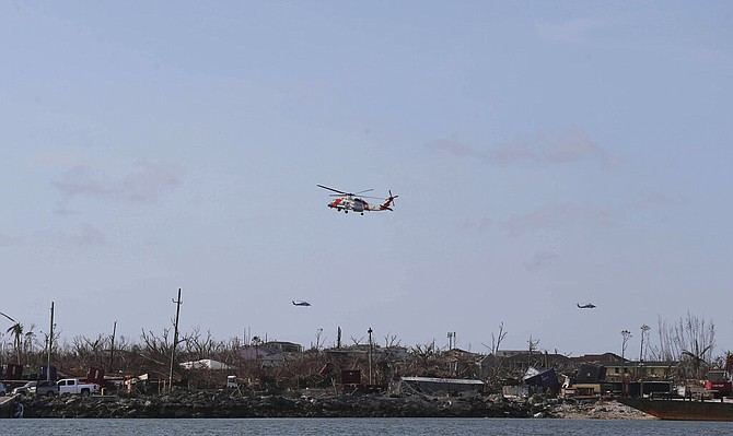 US Coast Guard helicopters fly over Marsh Harbour on Sunday. (AP Photo/Fernando Llano)