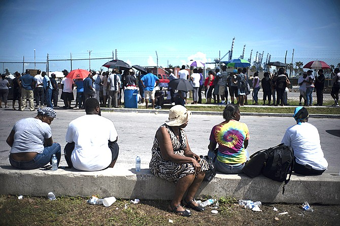 People gather at the port for aid sent by family members and friends in the aftermath of Hurricane Dorian in Freeport, Tuesday. (AP Photo/Ramon Espinosa)