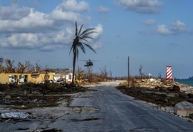 A helicopter flies over High Rock after delivering emergency supplies in the aftermath of Hurricane Dorian in Grand Bahama, Tuesday. (AP Photo / Ramon Espinosa)