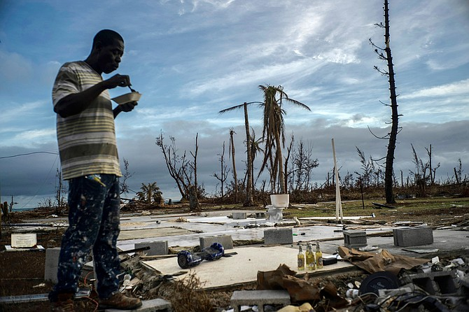 Jeffrey Roberts, 49, eats a plate of food while searching through the rubble of his relatives' home in Pelican Point, Grand Bahama, Saturday. (AP Photo/Ramon Espinosa)