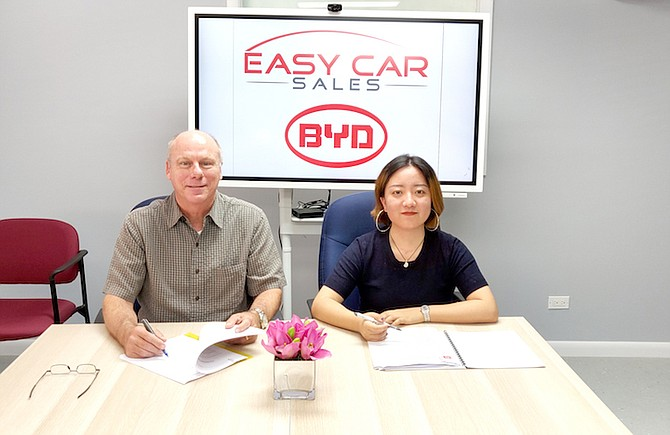 John Farmer, Director of Easy Car Sales, signs an agreement with Neva Zhang, representative for BYD, the largest producer of 100% electric vehicles in the world, to offer their complete range of products and post-sales support in The Bahamas.