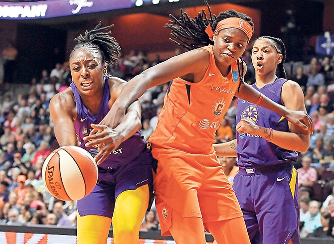 Los Angeles Sparks' Nneka Ogwumike, left, and Connecticut Sun's Jonquel Jones reach for a loose ball as Los Angeles Sparks' Candace Parker, right, defends during the first half of Game 1 of their WNBA semi-finals series last night in Uncasville, Connecticut.  (AP Photo/Jessica Hill)