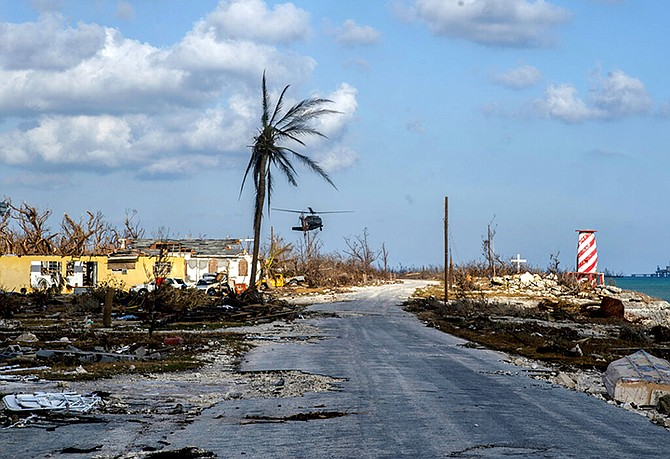A helicopter flies over the village of High Rock after delivering emergency supplies in the aftermath of Hurricane Dorian In High Rock, Grand Bahama, Tuesday, September 10. (AP Photo / Ramon Espinosa)