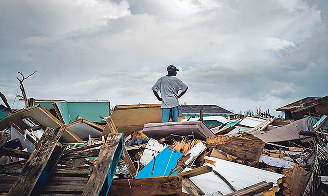 A man stands on the rubble of his home in a shanty town in Abaco after the passage of Hurricane Dorian. Photo: Ramon Espinosa/AP