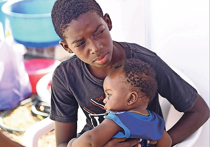 Two youngsters of Haitian descent in Marsh Harbour, Abaco, yesterday. The Tribune canvassed residents to see how they were coping with life after Hurricane Dorian's passage. 