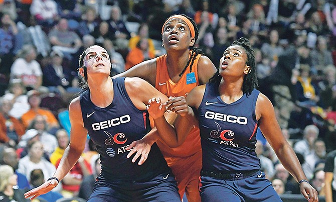 Connecticut Sun's Jonquel Jones, centre, fights for position under the basket between Washington Mystics' Elena Delle Donne, left, and Ariel Atkins, right, during the first half last night in Game 4 of the WNBA Finals in Uncasville, Connecticut.