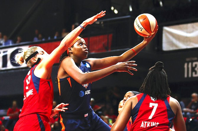 Connecticut Sun forward Jonquel Jones, centre, shoots between Washington Mystics forward Elena Delle Donne, left, and guard Ariel Atkins during the first half of Game 5 of basketball's WNBA Finals, Thursday, in Washington. (AP Photo/Alex Brandon)