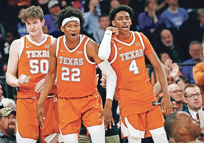 Texas centre Will Baker (50), forward Kai Jones, and guard Donovan Williams react on the sideline after guard Matt Coleman III drew a foul during the second half against California in the 2K Empire Classic on November 22 in New York.