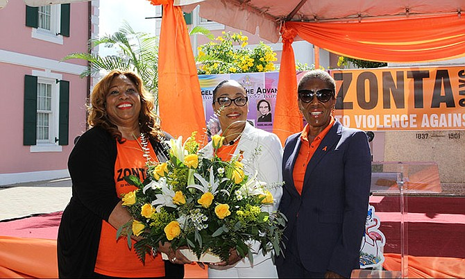 Kayla Darville (centre) presents a bouquet to the Prime Minister's wife, Patricia Minnis, along with National Advocacy Campaign Coordinator, Marisa Mason Smith.