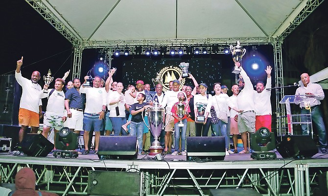 Minister of Agriculture and Marine Resources Michael Pintard presents the trophy to Running Tide, winners of Class A at the Best-of-the-Best Regatta in Montagu Bay over the weekend.