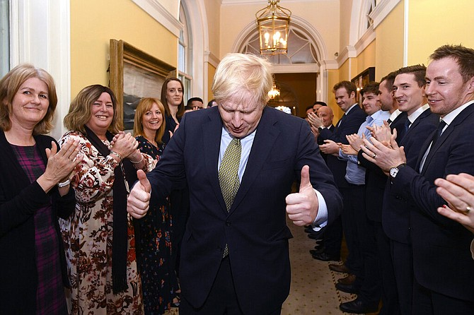 Britain's Prime Minister Boris Johnson is greeted by staff as he returns to 10 Downing Street, London, after meeting Queen Elizabeth II at Buckingham Palace and accepting her invitation to form a new government, Friday. Boris Johnson led his Conservative Party to a landslide victory in Britain's election that was dominated by Brexit. (Stefan Rousseau/PA via AP)