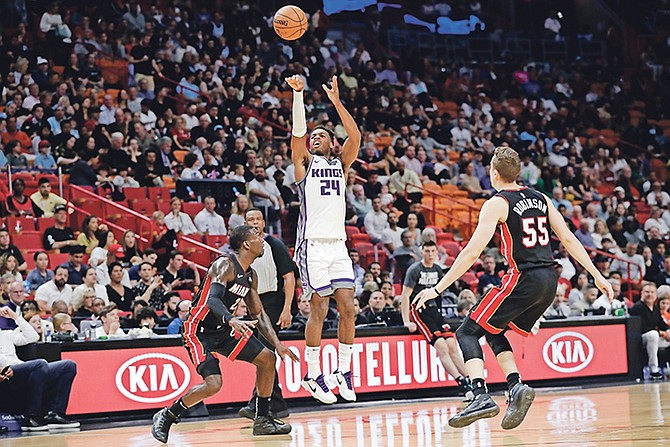 Kings guard Buddy Hield (24) attempts a 3-pointer over Heat guard Kendrick Nunn, left, and forward Duncan Robinson (55) in the first half last night in Miami. Hield scored 20 points with seven rebounds, seven assists, three steals and two blocked shots.  (AP Photo/Lynne Sladky)