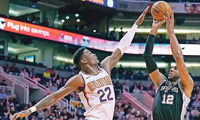 San Antonio Spurs centre LaMarcus Aldridge (12) shoots over Phoenix Suns centre Deandre Ayton during the first half on Monday night in Phoenix. (AP Photo/Rick Scuteri)