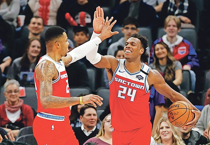 Sacramento Kings' Kent Bazemore, left, and Buddy Hield celebrate in the closing moments of the Kings' 122-102 win over the San Antonio Spurs in in Sacramento, California, on Saturday, February 8. Hield became the fastest player in NBA history to reach 800 career 3-pointers, doing it in 296 games.  (AP Photo/Rich Pedroncelli)