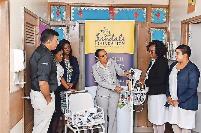 Dr Marcia Bassett of Princess Margaret Hospital (centre) explains to Sandals and hospital staff how the vital sign monitor works.