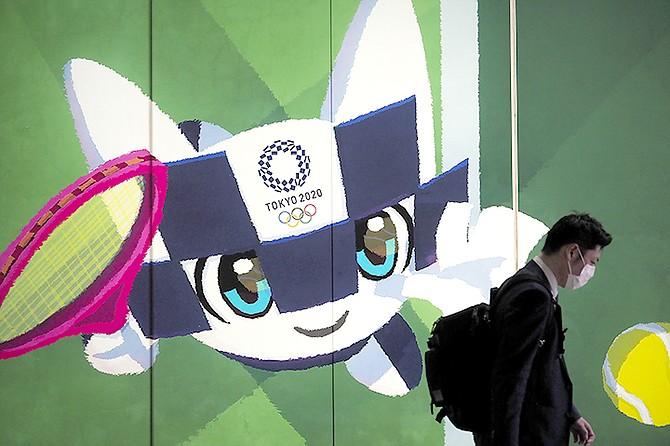 A pedestrian walks past a large display promoting the Tokyo 2020 Olympics in Tokyo, last week. (AP Photo/Jae C. Hong)
