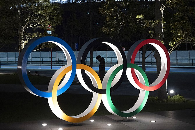 A man is seen through the Olympic rings in front of the New National Stadium in Tokyo, Tuesday.