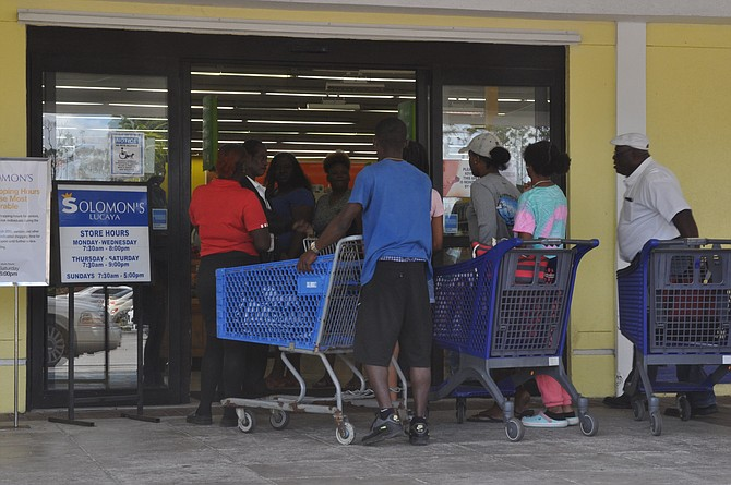Shoppers look a bit too close together in Grand Bahama yesterday.