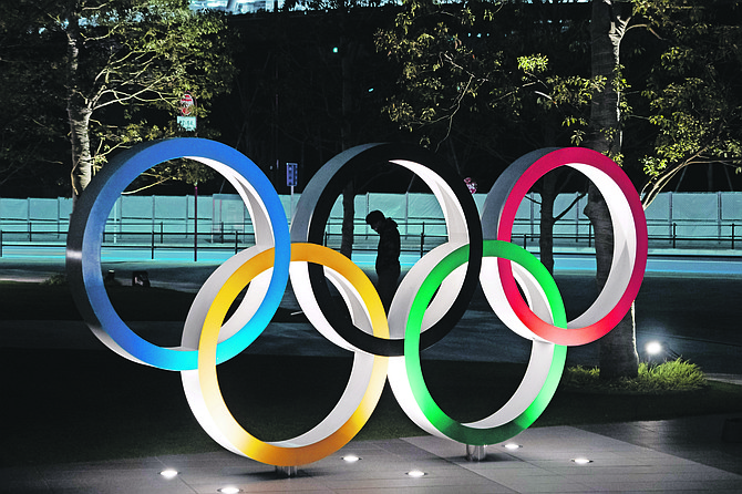A man is seen through the Olympic rings in front of the New National Stadium in Tokyo yesterday.
