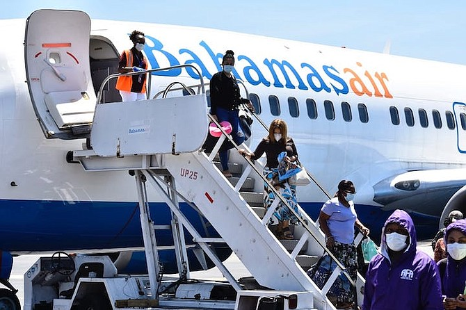 Returning nationals and residents arrive in The Bahamas on Friday.