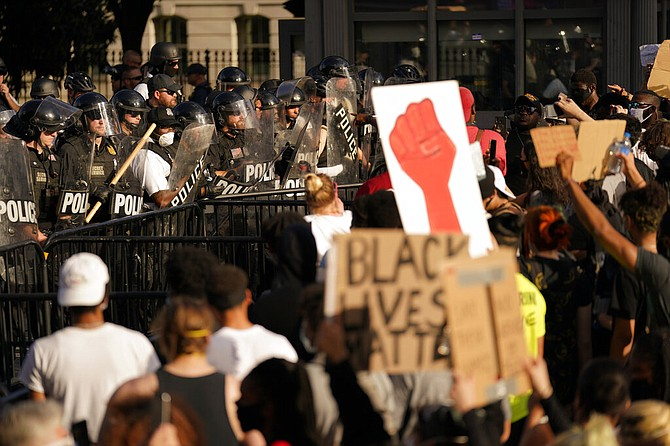 Demonstrators stand in front of police in riot gear as they gather to protest the death of George Floyd, Saturday, near the White House in Washington. Floyd died after being restrained by Minneapolis police officers. (AP Photo/Evan Vucci)