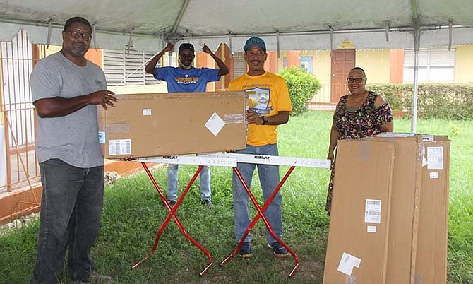 WHITTINGTON BROWN, of the Class of 1988, presents the boxes of hurdles to Ainsworth Beckford, athletic director, as physical education teacher Jameison Pratt and acting principal Lisa Miller look on.