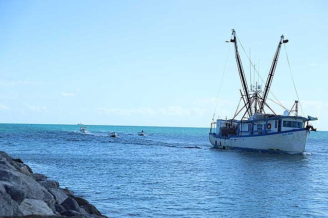 A Bahamian fishing vessel with several skiffs makes its way into HMBS Coral Harbour after the crew and vessel were apprehended for fishing violations, fishery products on one of the vessels, a compressor on one of the vessels, and a skiff with a compressor.