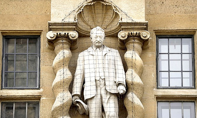 A statue of Cecil Rhodes stands mounted on the facade of Oriel College in Oxford, England.